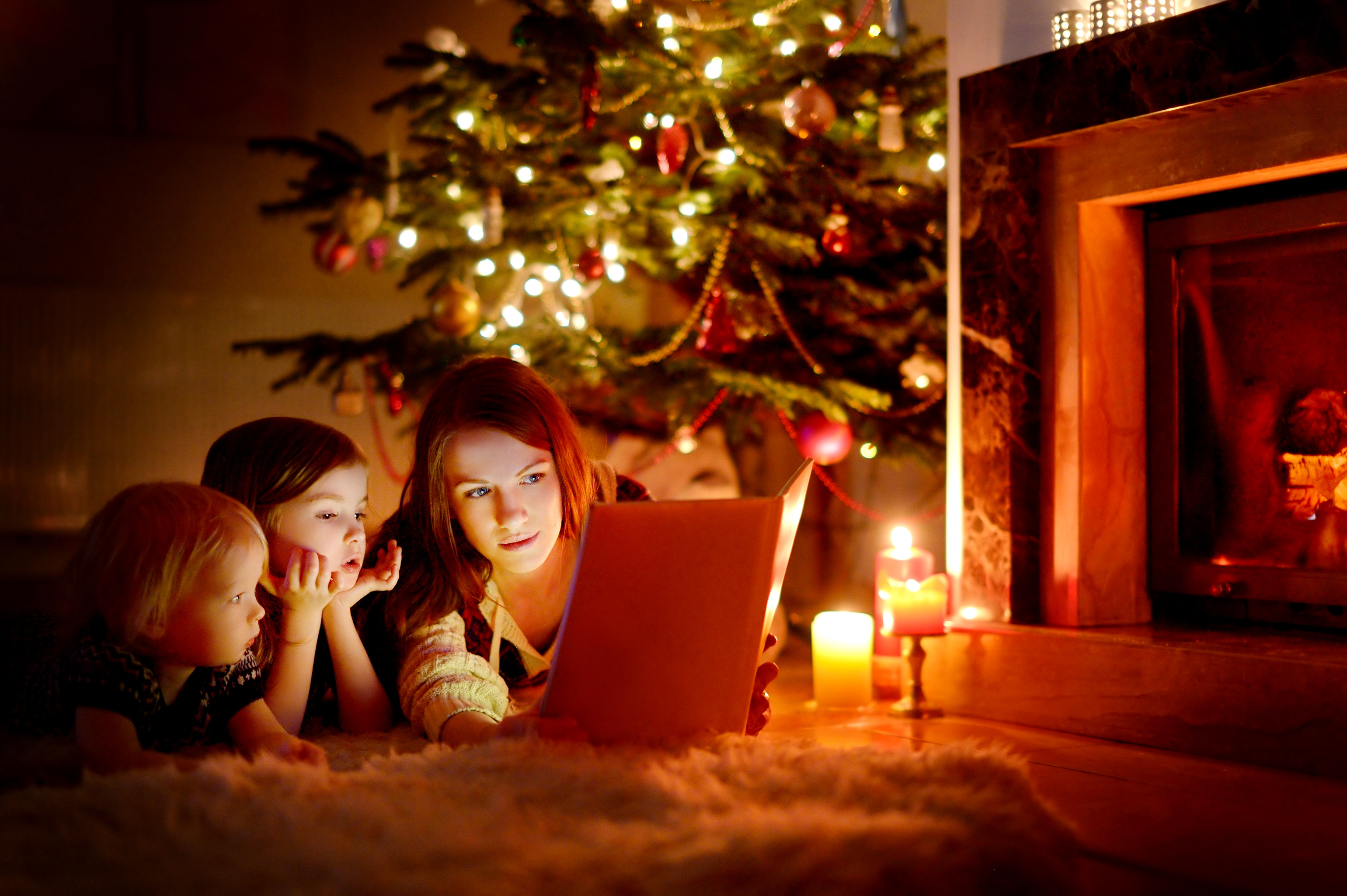 mother-and-daughters-reading-book-on-christmas