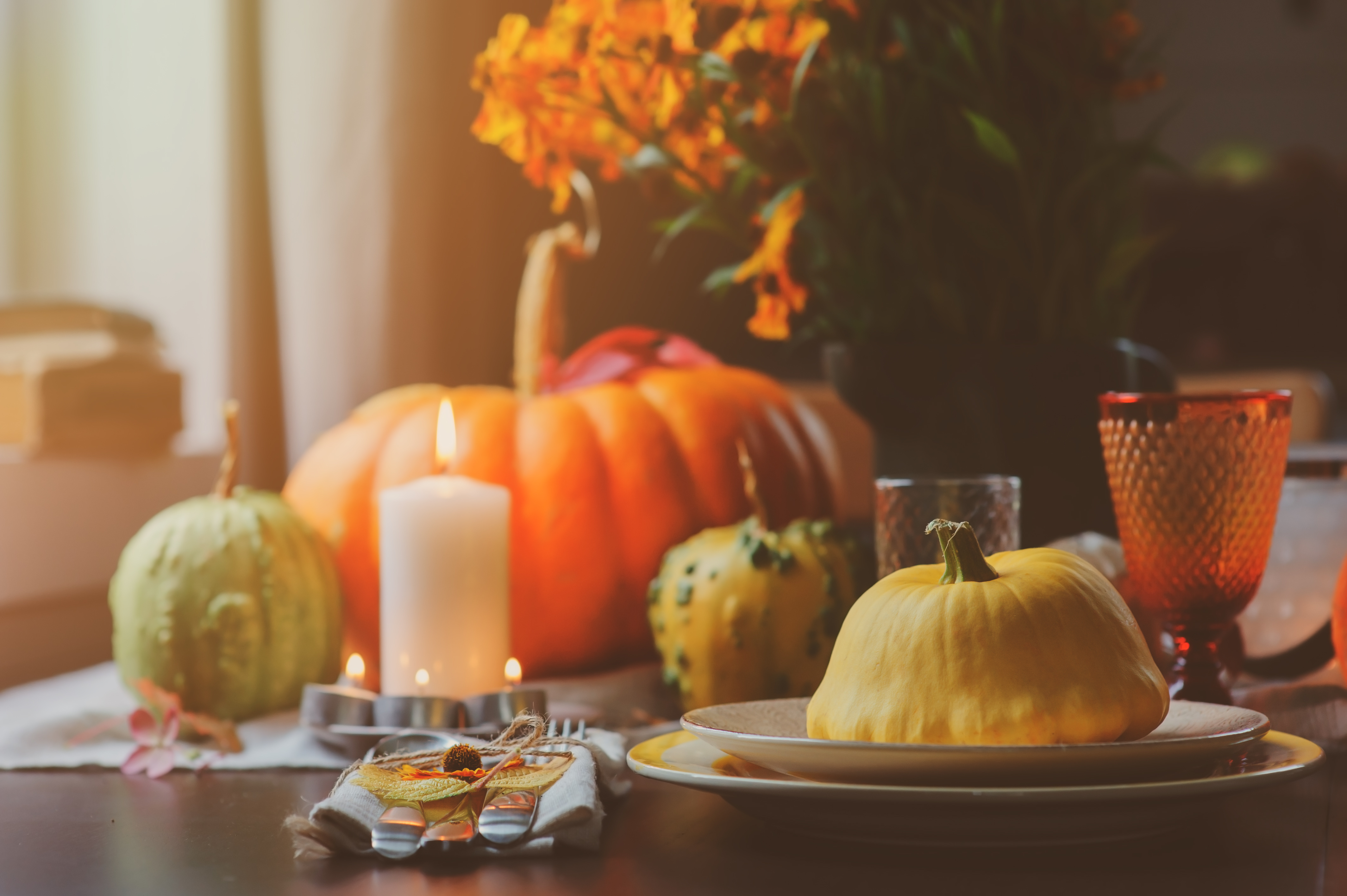 autumn traditional table setting for Thanksgiving or Halloween, with candles squash and pumpkins.