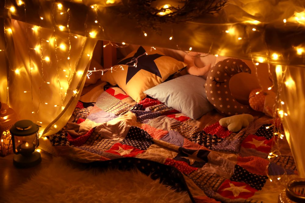 blanket fort with string lights and pillows