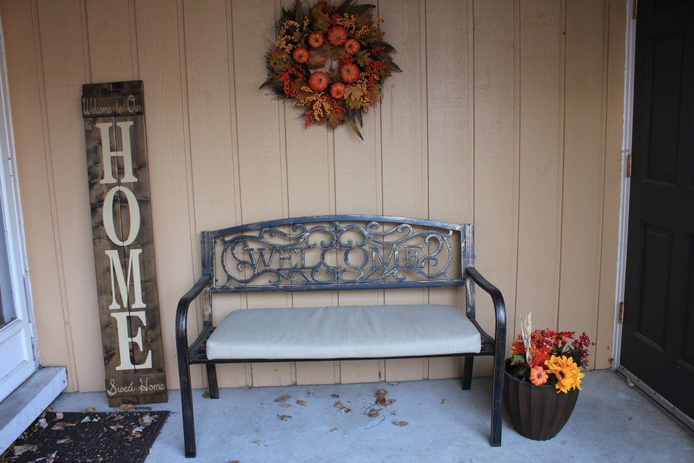 How To Make Your Porch Cozy For Fall - use fall wreaths and florals